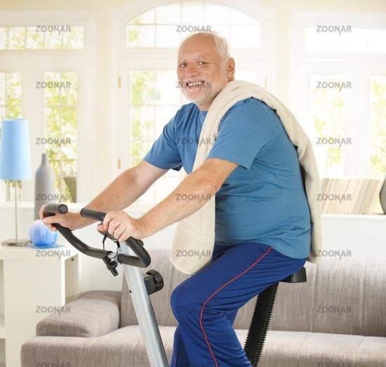 Senior man smiling on fitness bike
