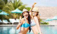 smiling women eating ice cream over swimming pool