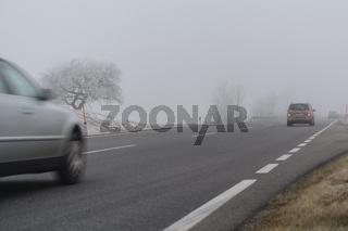 Autos fahren bei schlechten Sichtverhältnissen im Herbstnebel