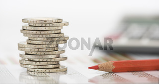 stacked euro coins and calculator laying on financial business chart of stock market