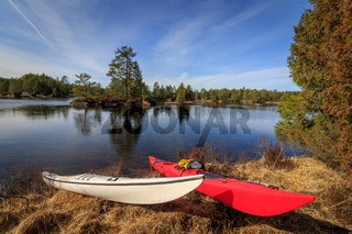 Two kayaks lying on the grass at the riverside in Nidelva, Norway