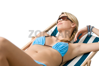 Beach - Young woman in bikini lying on deck chair