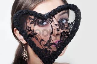 Close-up portrait of beautiful young woman looking throught a lace heart