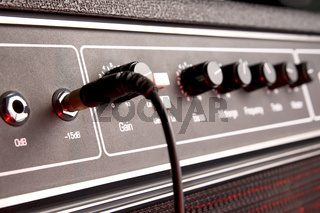black guitar apmlifier panel with jack and cable