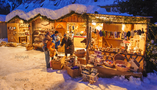 Romantic Christmas market in Bavaria with decorated and illuminated huts in the snow
