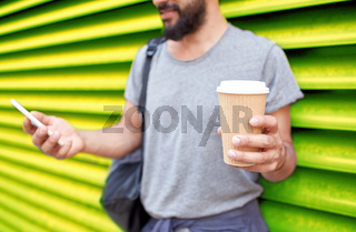 man with coffee cup and smartphone over wall
