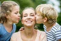 Kinder küssen Mutter am Muttertag