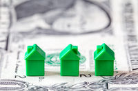 Miniature houses on dollar banknote background