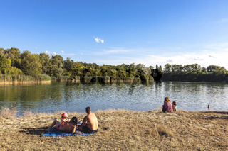 Family enjoying the summertime at a lake in a natural reserve park in Vienna