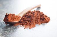 Dark cocoa powder in wooden scoop.