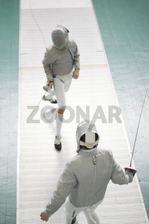Two young fighters in protective mask fighting at the fencing competition