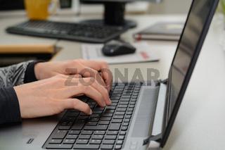 Büroangestellte tippt auf Tastatur eines Laptops - Nahaufnahme