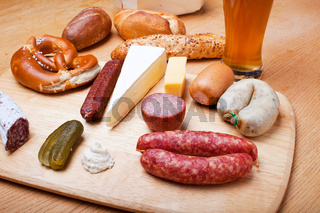 Wurst, Brot und ein Weißbier auf einem Eichentisch