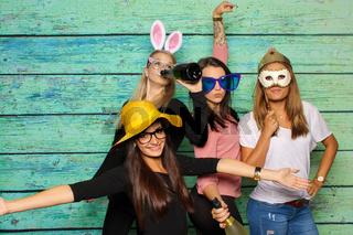 4 junge frauen posen vor einer fotobox herum