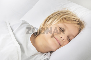 Smiling boy sleep in bed