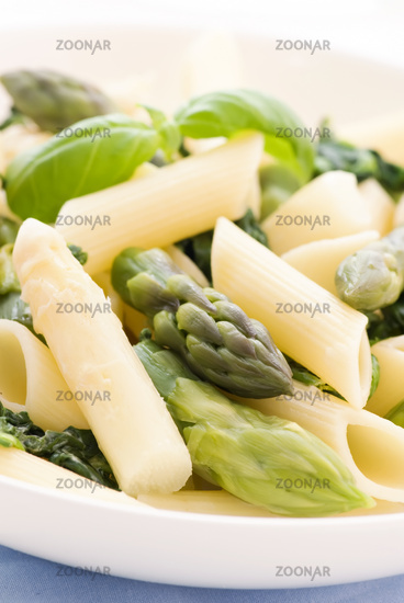 Italian noodles with asparagus spears as closeup on a white plate