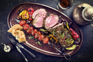 Barbecue Lamb Roast with skewered tomatoes and olives as close-up on a plate