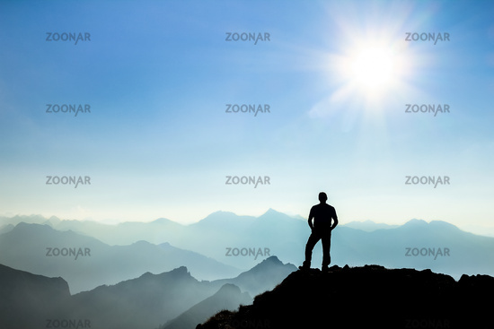 Man reaching summit enjoying freedom and watching towards mountain ranges.