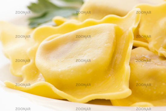 Boiled ravioli with parsley as closeup on a white plate