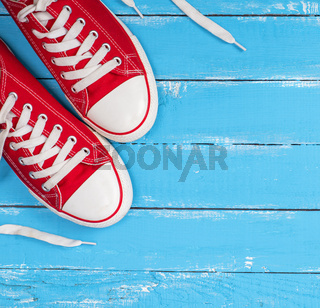 pair of red textile sneakers with white laces