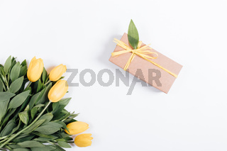 Box with a gift and yellow tulips on a white background
