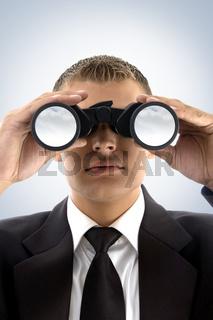 young businessman using binoculars