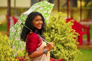 Indian girl In sari walking in the rain with umbrella, Pune, Maharashtra