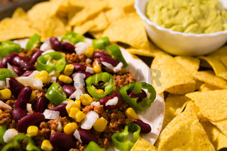 Closeup of Mexican tortillas with meat, red beans, Jalapeno pepper and nachos chips