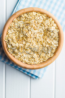 Dry rolled oatmeal in wooden bowl.