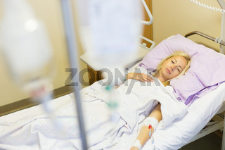 Bedridden female patient recovering after surgery in hospital care.