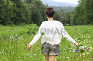 Happy pretty brunette woman in chamomile field
