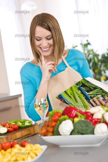 Cooking - Smiling woman holding cookbook, with vegetable and pasta