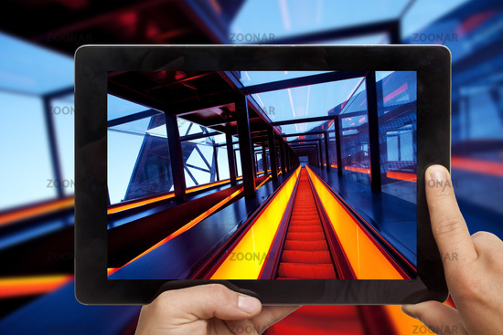 holding a tablet PC in the hands with a photo of gangway of Zollverein in front of the orginal