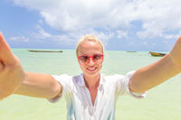 Beautiful young woman doing selfie on tropical beach.