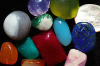 Multi-colored semi-precious stones on black close-up