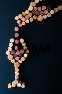 Filling a glass of wine from the bottle made by cork vertical