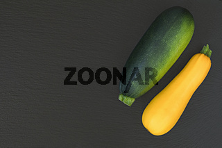 Fresh green zucchini and yellow zucchini on a black stone surface.  Top view, copy space. Healthy eating concept.