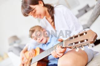Junge übt auf der Gitarre zu spielen