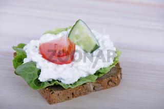 Vollkornbrot mit Huettenkaese, Salatblatt, Gurke, Tomate