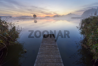 Wooden Jetty with Reflective Sky in Lake at Dawn