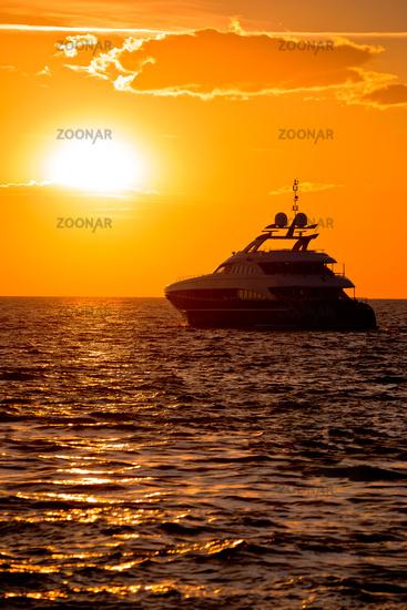 Luxury yacht on open sea at golden sunset