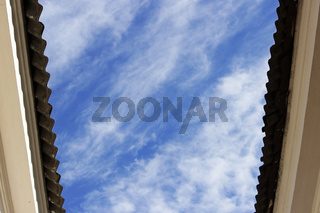 canopy roof of the houses with a wavy roofing material on a background of blue sky with clouds in summer
