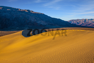 The woman with camera have difficulty climbing dune
