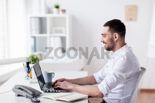 happy businessman with laptop at office