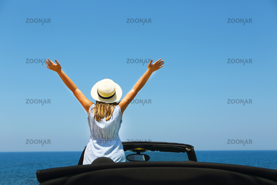 Happy young woman in car on the beach
