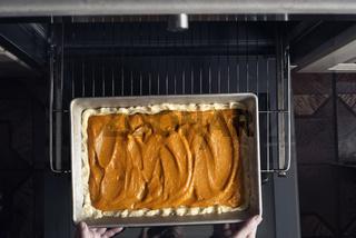 Putting pumpkin pie in the  oven horizontal