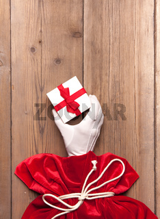 Santa Claus hand give a present from the red bag on Old Wooden Background