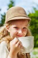 Blondes Mädchen mit Hut hat Durst