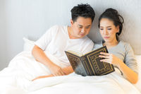 Couple reding book in bed