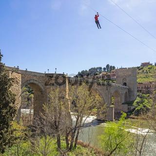 Eine Person schwebt an einer Seilbahn über den Fluss Tajo, Toledo, Spanien